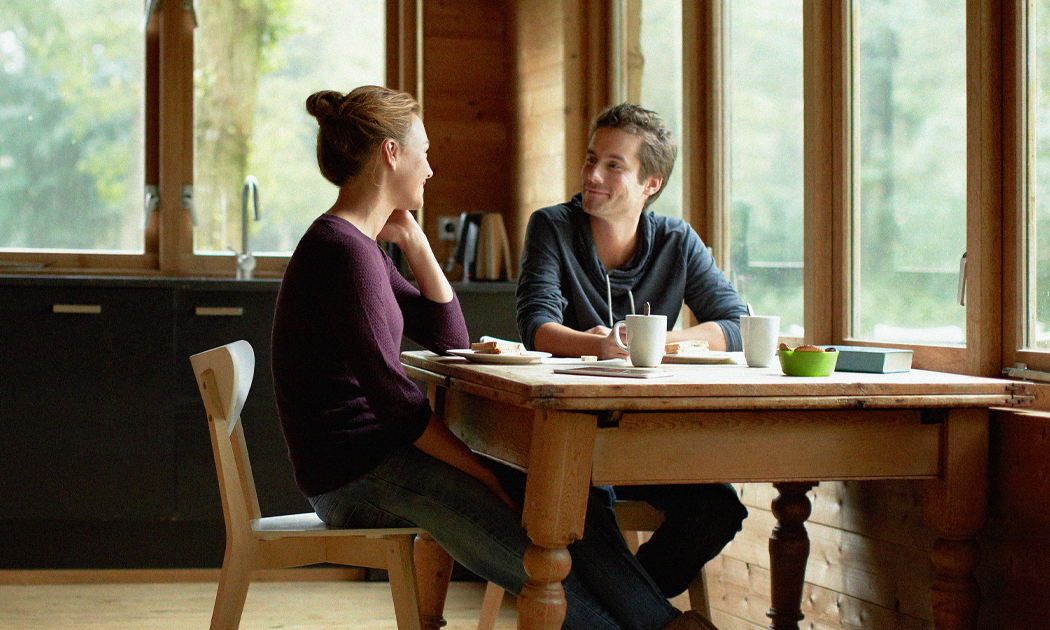 younger couple talking at a kitchen table