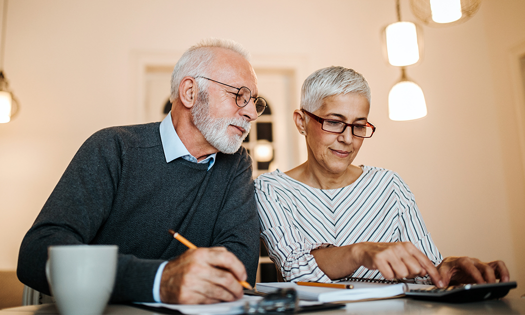 Older couple budgeting in kitchen with coffee