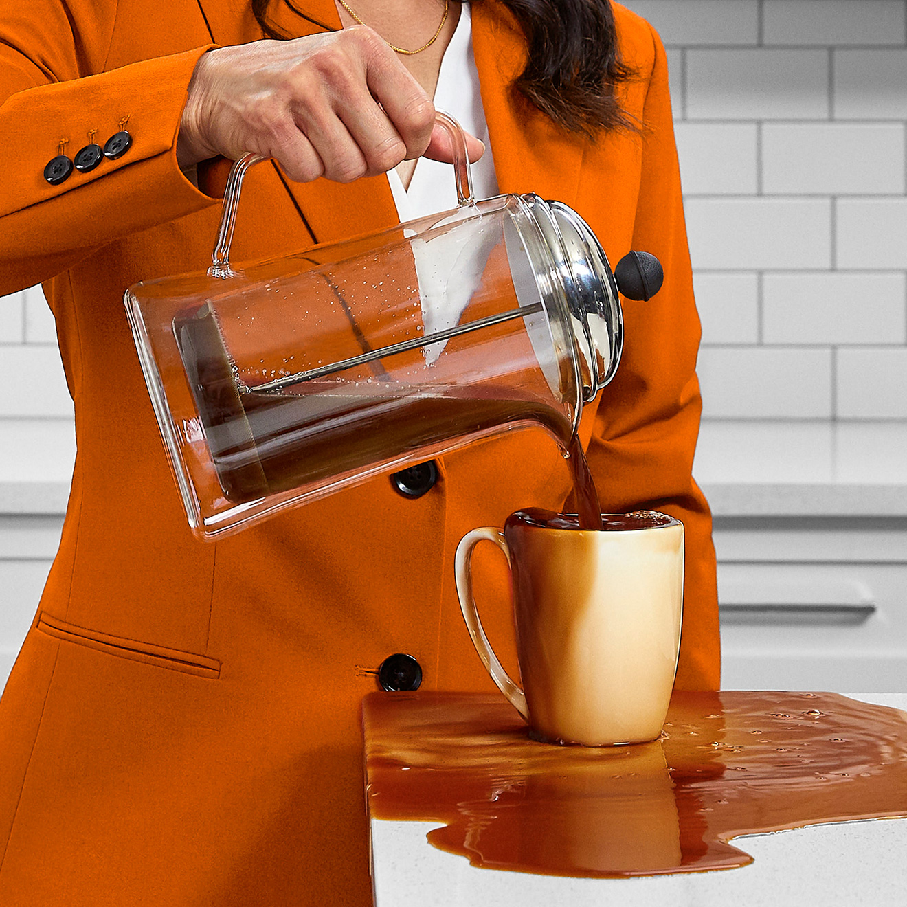 Woman in an orange suit pouring coffee into overflowing cup
